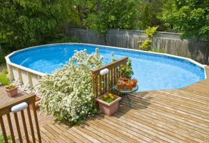A beautiful above-ground pool set-up with hidden pool equipment.