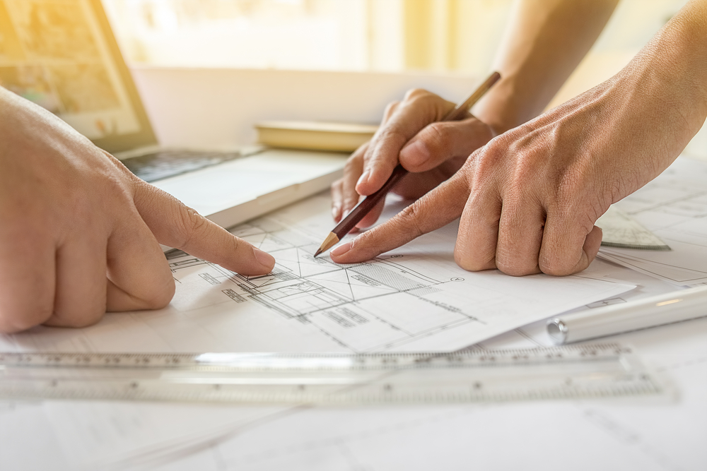 Close up of two people looking over home construction blueprints