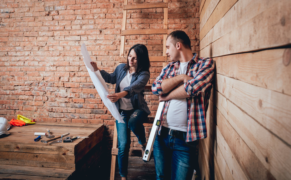 couple looking over renovation plans... perhaps thinking about home insurance needs